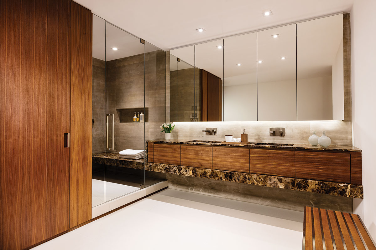 Eurostar's Emperador brown marble reinforces the home's sculptural appeal as it flows from the master bath's vanity to the shower bench. Opustone's blocks of Autumn Ashes wrap the shower in spa-like serenity, while Nuevo's wood-slat bench enhances the ambiance in the open area.