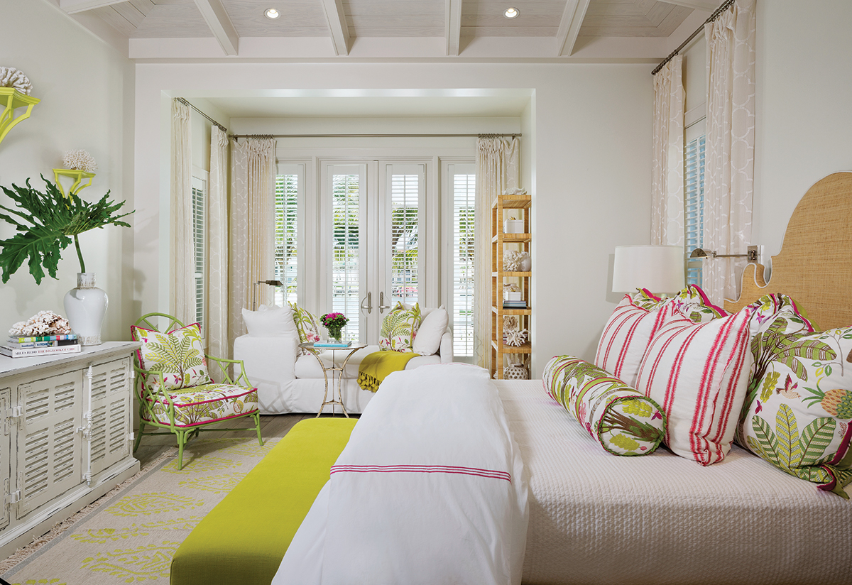 The Palm Beach-inspired master bedroom has a tropical feel created with floral accent pillows and a Mecox Garden chair framed in a chartreuse hue. A weathered white dresser recalls the paneling used throughout the home.