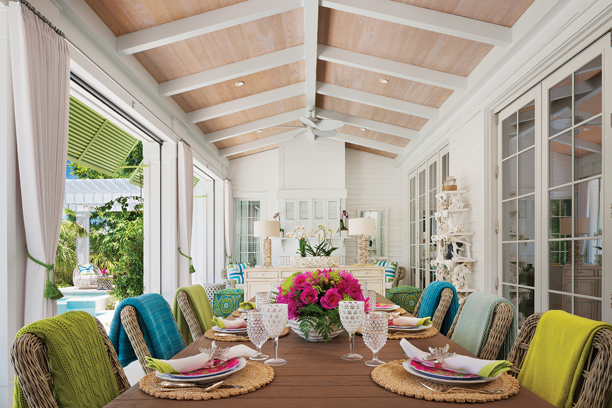 Bright color prevails on the loggia. Wicker chairs covered with chartreuse-and-turquoise throws edge an expansive table and chairs from JANUS et Cie. Two table lamps comprised of crushed oyster shells and driftwood shelving flanked by French doors pay homage to the nearby sea.