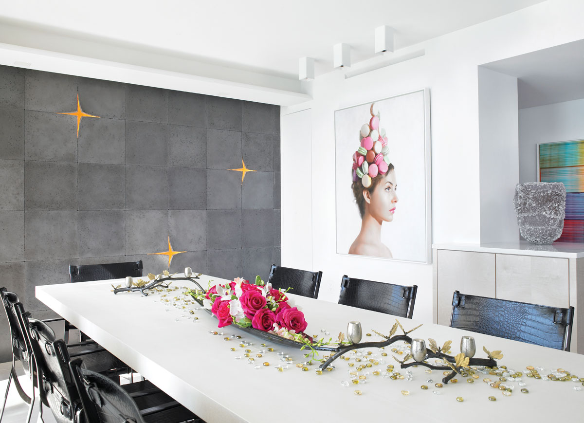 """In the dining area, an intriguing glass centerpiece branches out across a Christian Liaigre dining table, where Fendi Casa's """"Blixen"""" dining chairs with hide belts and gunmetal gray buckles pull up to join the party. A dynamic composition of three-dimensional Kwa concrete tiles by Itai Bar-On from Ann Sacks covers a focal wall, while a whimsical painting, The Macaron Hat by artist Will Cotton, adds the perfect touch of flavor."""