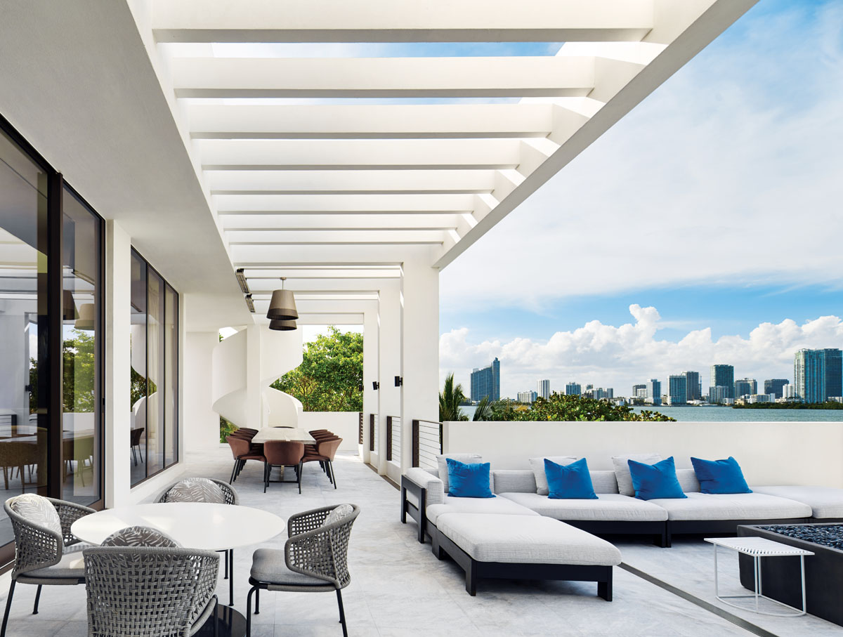 Scenes of the Miami skyline and the Biscayne Bay shoreline are the raisons d'etre for a dramatic floorplan reversal that sites a balcony on the upper level of this San Marco Island home. With an array of Minotti outdoor furnishings and an E.M. Soberon dining table, the homeowner sought a palette to echo the lush tropical setting.