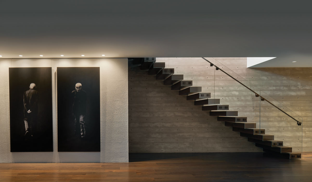Designed by A BOHEME Design and crafted by Living Design Studios, each tread of the stairway, cantilevered from a board-formed concrete wall, is encased in French country walnut. A glass and bronze railing emanates the illusion of floating.