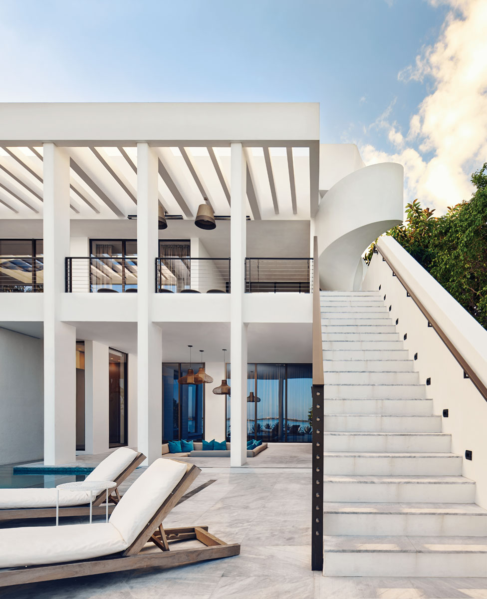 A brise soleil wraps around the home's exterior. A BOHEME designed the element to unify outdoor spaces, while functionally deflecting sunlight. The clever scheme also creates a multitude of light and shade patterns reflected throughout the house. The stair landing links the pool to the upper-level balcony, while a helical stairway continues on to the roof for even more fabulous views of skylines and waterways.