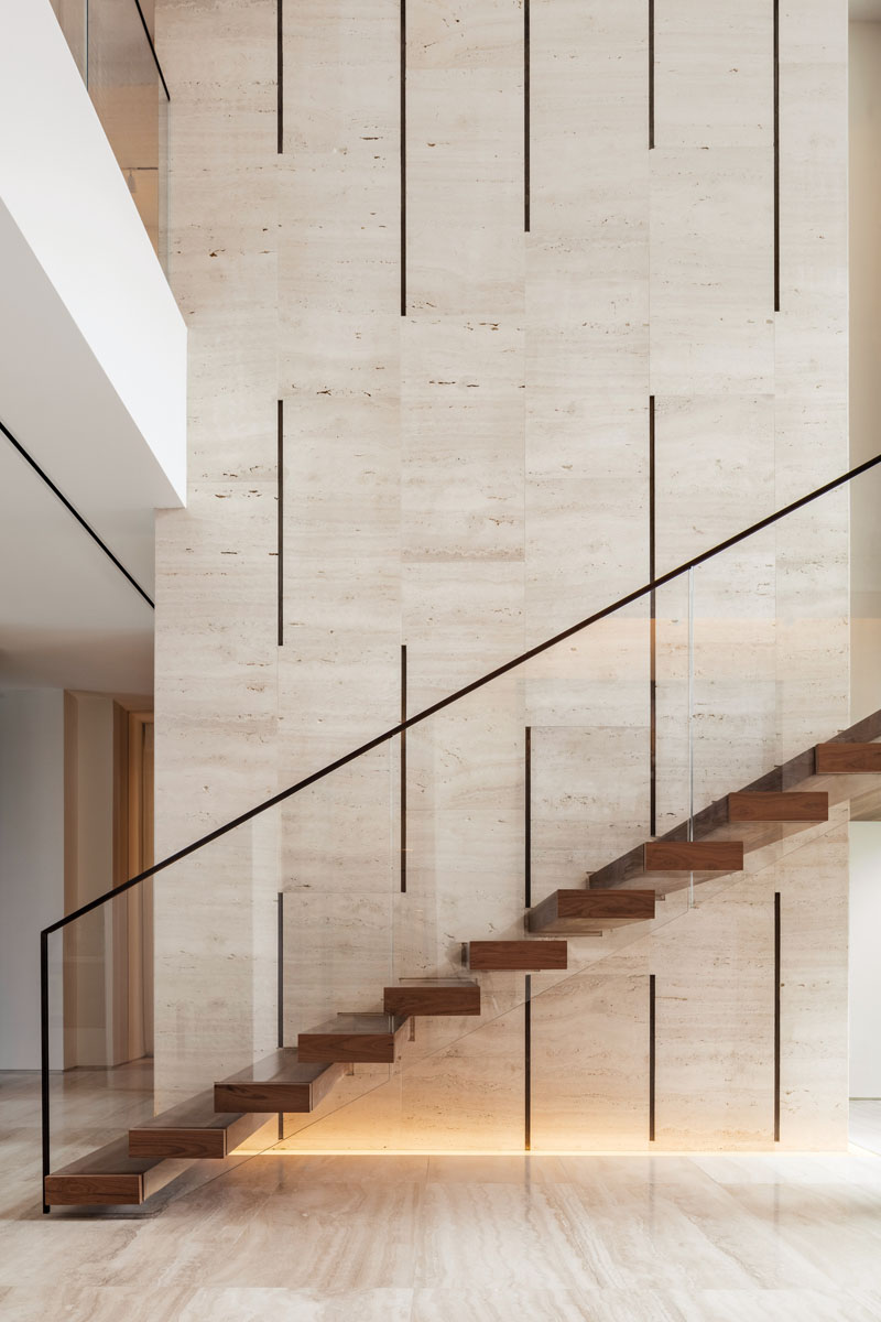 Asserting its own design nearby, the bronze elements of the travertine wall, the resonating bronze of the stairway's handrail and its clear glass balustrades, and the thick walnut treads insist on being seen.
