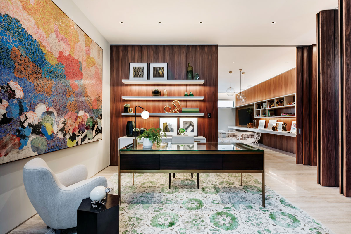 "Though the owners specified the walnut paneling, the designer opted to ""lighten"" certain areas. In the wife's office, the simple introduction of white shelving, Holly Hunt's deep-seated white armchair, Zhuang Hong-yi's art from Smith Davidson Gallery and Niba's softly muted area rug add brightness."