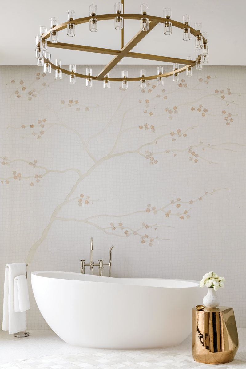 """Nacre,"" also known as mother of pearl, grounds the master bath, while a glass mosaic of cherry blossoms climbs the wall to the reimagined Art Deco form of the ""Ravelle"" chandelier from Restoration Hardware. Waterworks' simple vessel tub and a sparkling golden accent table only divert the eyes for a moment, before the wall and its organic origins call us back."