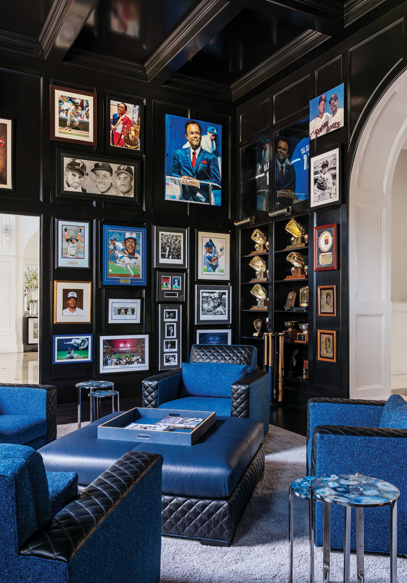 """In Roberto's study, memorabilia and awards gleaned during his 16-year baseball career pop from the black lacquered surfaces. """"The walls create a dramatic and masculine backdrop,"""" interior designer Jennifer Marksberry says. """"The touches of blue honor Robbie's career with the Toronto Blue Jays."""""""