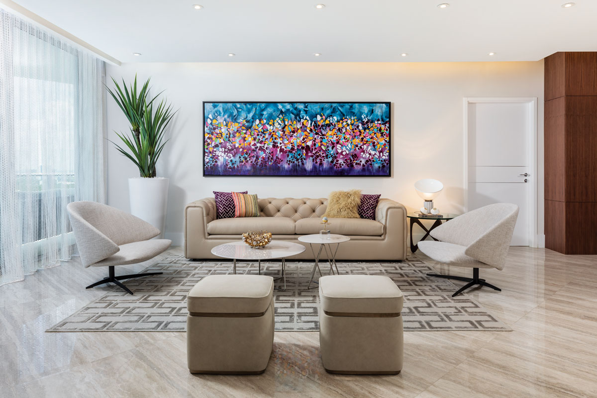 """Mix-and-match sets the tone in the living area, where the """"Kost"""" chairs and """"Dubli"""" cocktail tables, both by Desiree, are of varying heights. A leather-clad sofa from Addison House and Artefacto's suede stools face off atop the geometric pattern of a silk area rug."""