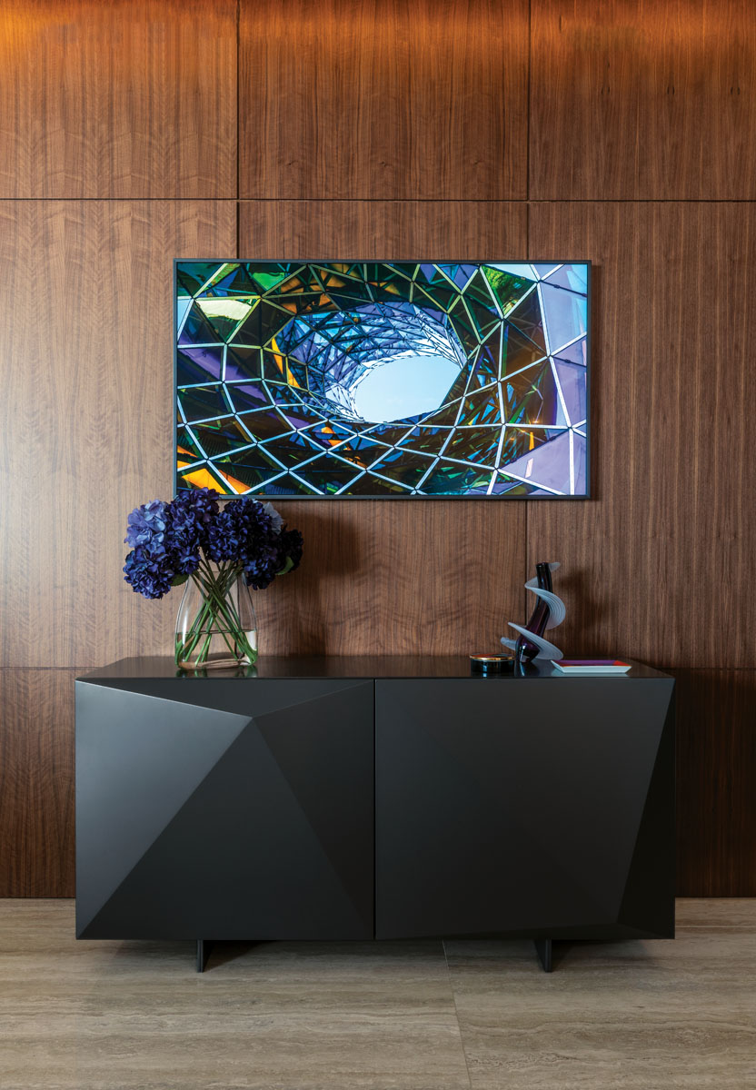 """Cattalan Italia's matte graphite cabinetry from Addison House styles the foyer in sleek, angular form. The """"Heechee Vase,"""" a blown glass vessel by Thomas Kelly, blends with the colors of the photo art above."""