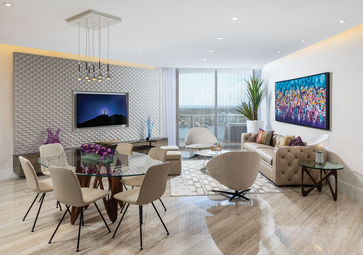 """Displaying more of the client's own art, Gomes placed another of his moody framed photos in the main living areas. """"He travels to find unusual scenes, then shoots them magically,"""" she says. A contemporary chandelier from Studio Italia Design illuminates the art and the dining area that comes alive at night."""