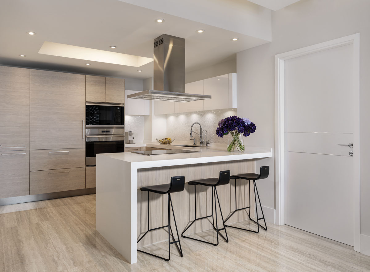Snaidero's two-toned cabinetry adds pizzazz to a small kitchen that looked simply white. The soffit located in the middle of the space is a perfect architectural feature to break it up, while stainless steel appliances from Miele serve to accent the culinary space. Cattelan Italia's black, metal-and-leather counter stools tuck neatly beneath the waterfall-edge island.