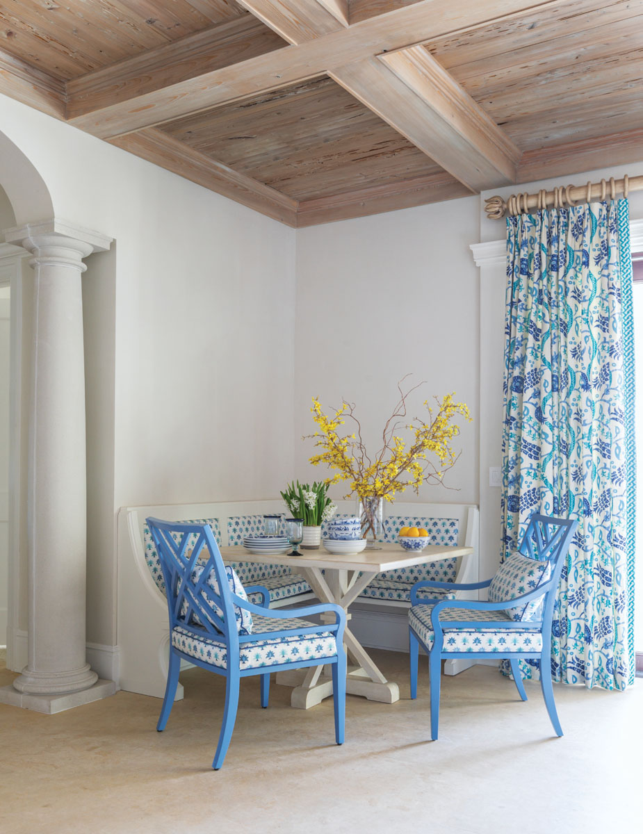 EJ Victor side chairs in blue pull up to a charming dining table from Tritter Feefer, while a custom banquette by Beaches Woodcrafts invites more fun into the family room. A laminated Mally Skok palm-print from Travis & Company covers the banquette and chairs, and Brunschwig & Fils' pattern from Kravet styles the draperies to embrace the home's overall color palette.