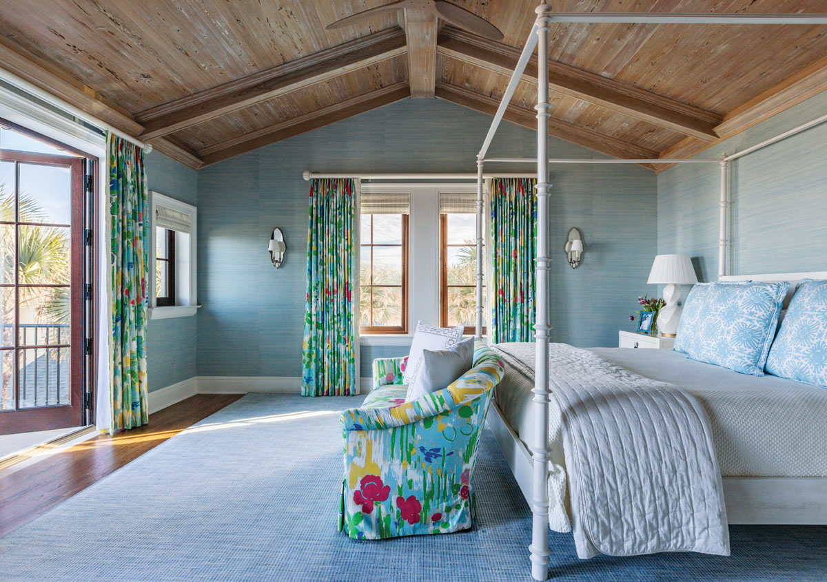 An ocean-blue grass cloth from Schumacher covers the walls in the master bedroom, where the draperies display Brunschwig & Fils' vintage print from Kravet. Lacquered bedside tables from Oomph Home and a white four-poster bed from Oly Studio lend a beachy ambience.