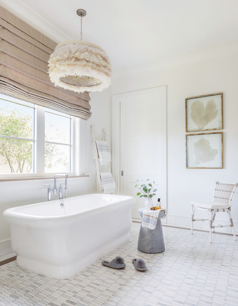"In ""her"" master bath, a Waterworks tub offers a deep soak beneath the eccentric ""Feather"" light pendant."