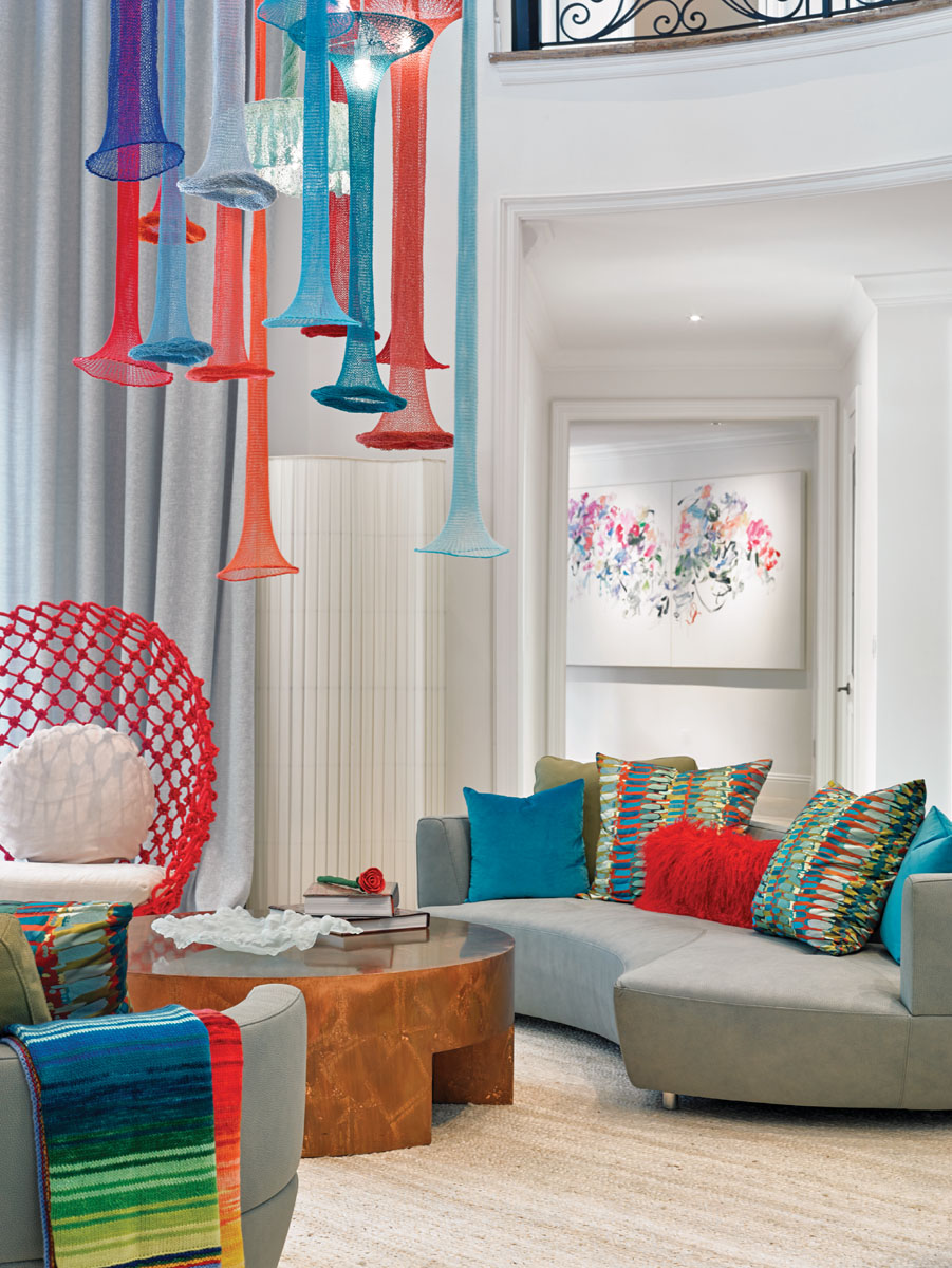 """Roche Bobois sofas and """"Dragnet"""" lounge chairs by Kenneth Cobonpue circle the living room. Linen-and-bamboo yarn luminaires suspend from 22 feet high."""