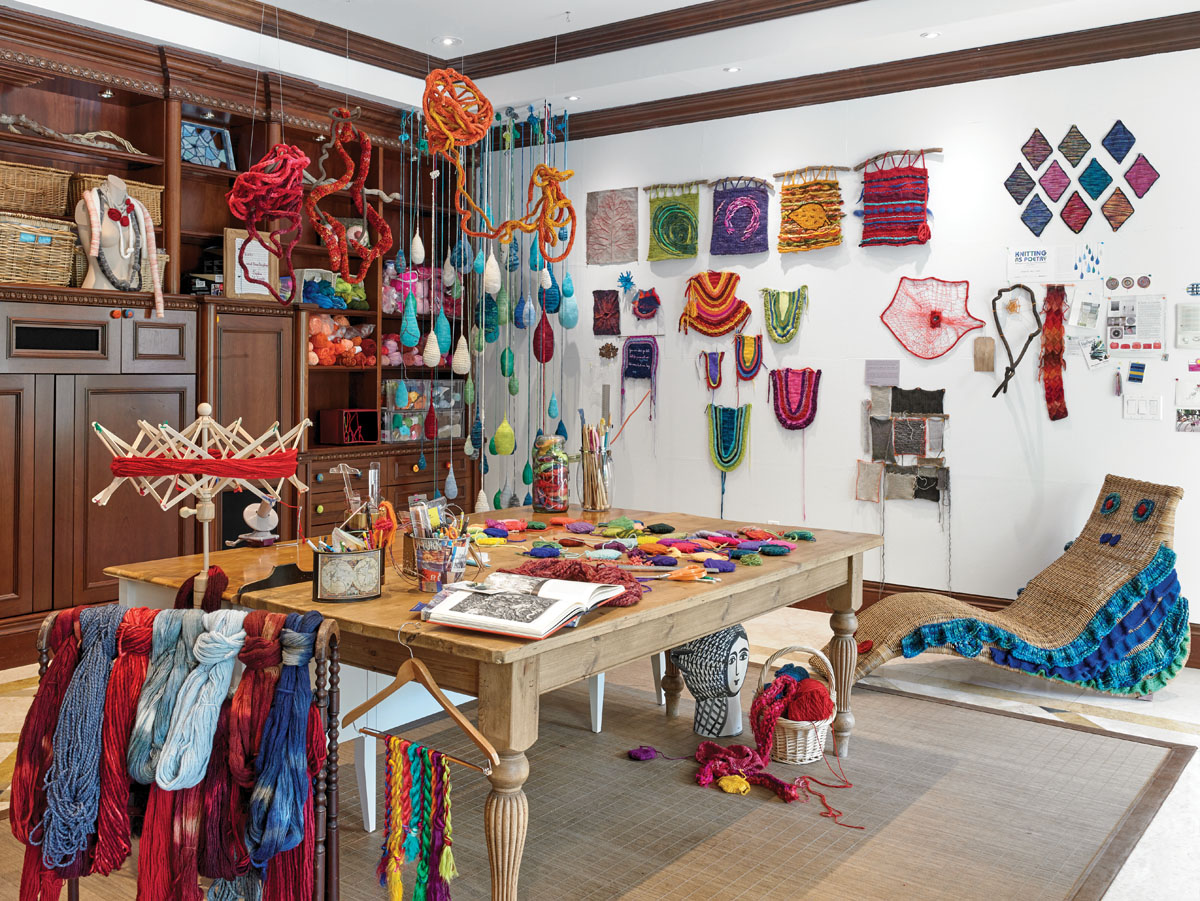"""In the art studio, shapes appear to mold into whimsical forms — some becoming smiling chaises, others brilliant """"smoke rings"""" or soft, knitted drops of rain."""
