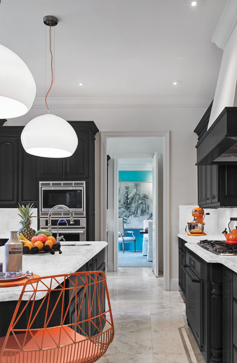 """The kitchen is a place of respite. The eye is drawn to splashes of orange that suspend glass globes from Circa Lighting, shape the midcentury wire form of Bend Goods' midcentury """"Lucy"""" counter stool."""