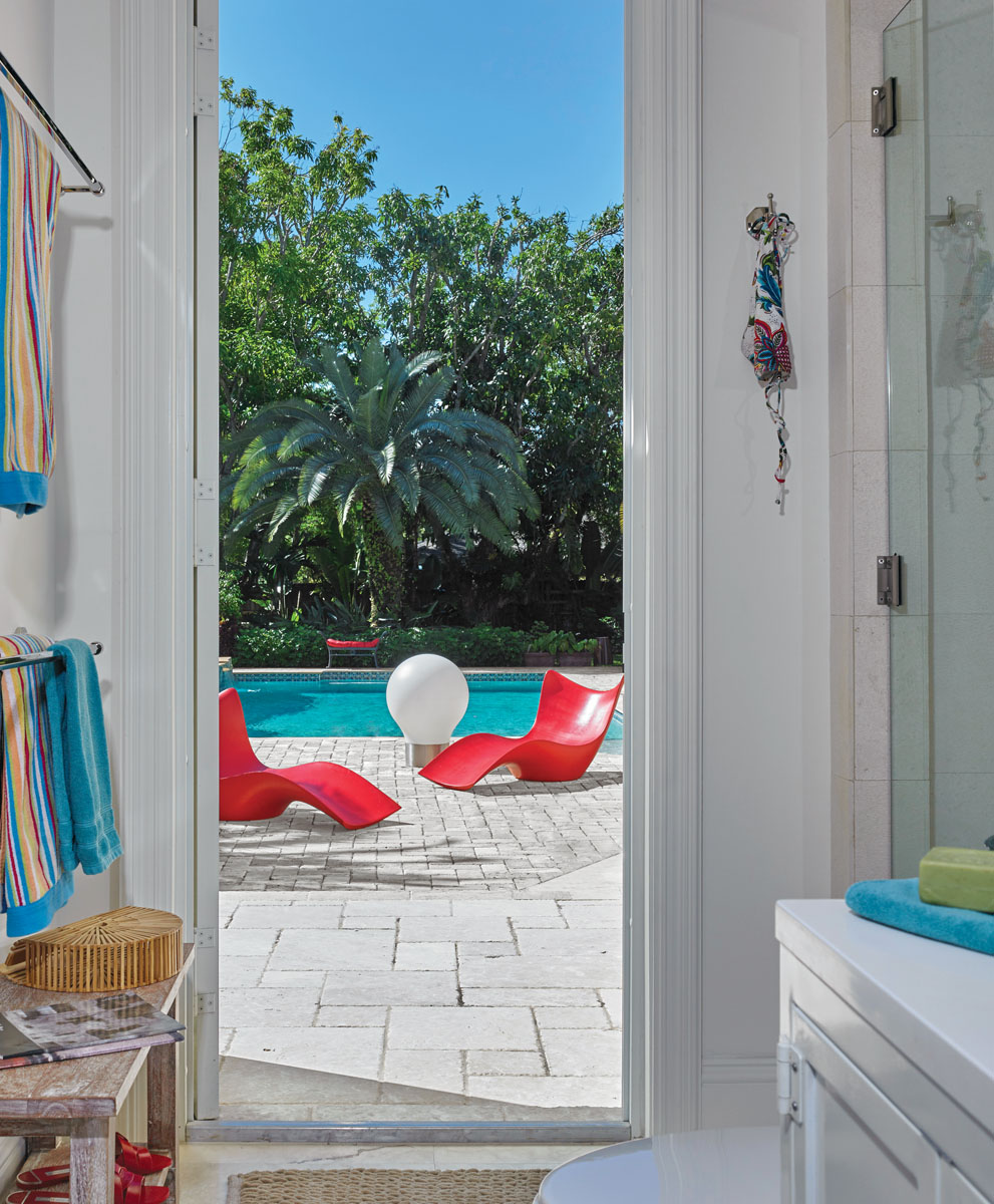 Complete with a new shower, cabinetry, lighting and flooring, this cabana bath opens to an inviting tropical vista with Karim Rashid's chaises from Studio Vondom reclining poolside.