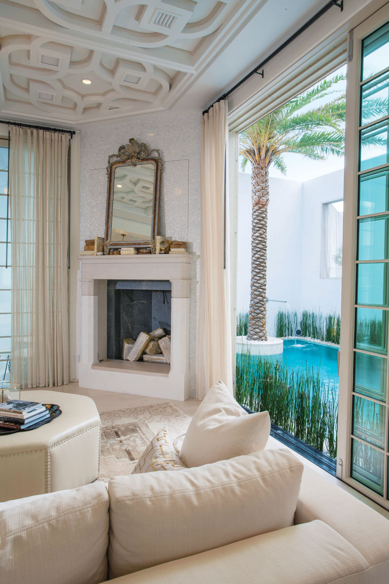 A French mirror, circa 1800s, and turn-of-the-century Italian theatre urns adorn the fireplace. Steps away, glass doors slide open to the floating pavilion on one side and the pool on the other.
