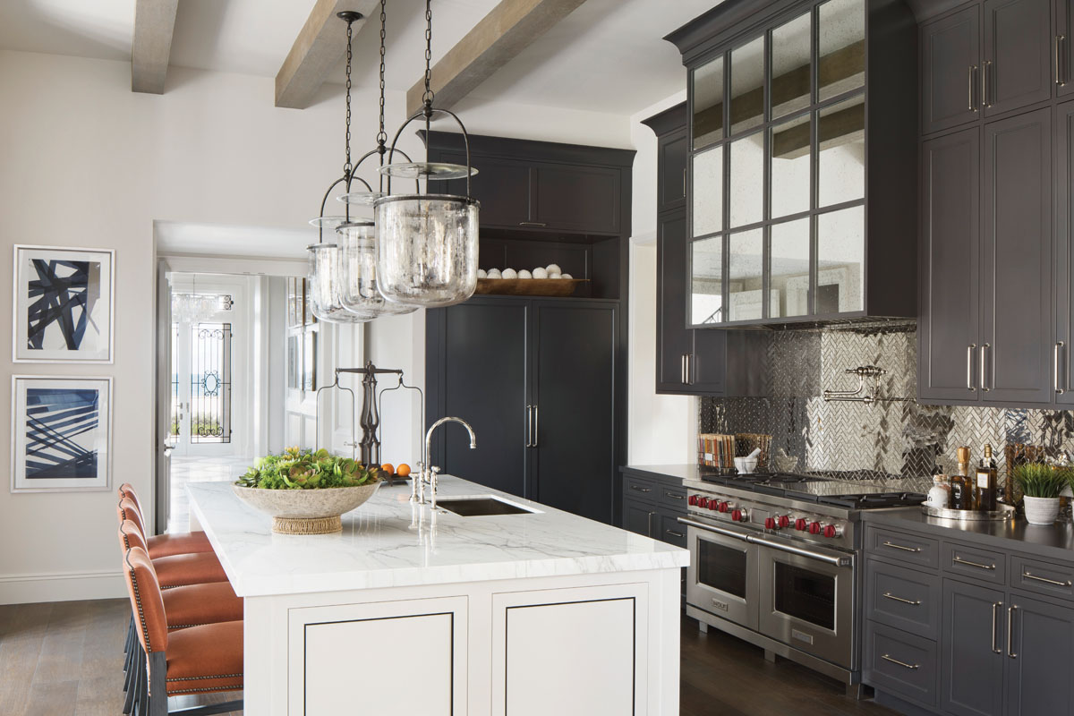 A trio of aged-iron lanterns from Visual Comfort; Porath's cabinetry that lines the culinary space.