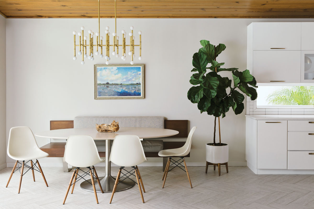 Eames fiberglass chairs circle Saarinen's oval dining table in the casual breakfast area, where a custom banquette fabricated by Stettinius Construction appears to float next to S&W Kitchen Supply's sleek, white cabinetry.