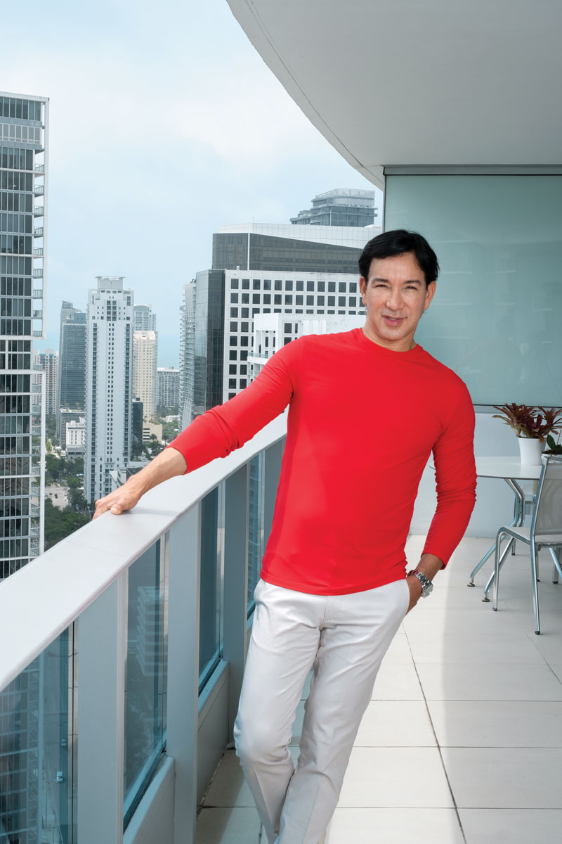 Looking dapper in his namesake lightweight red sweater and white slacks, fashion designer René Ruiz enjoys dining alfresco on the glass-railed terrace of his condo on the 43rd floor of the Epic Residences.