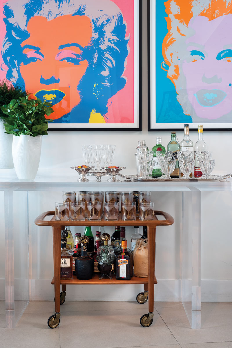 """The bar station acts as a transition space for the designer's parties. """"The 1950s wood bar caddy is quintessentially American and harkens back to a simpler time,"""" Ruiz says. Atop KOM's custom console sits a white crystal vase from Two's Company."""