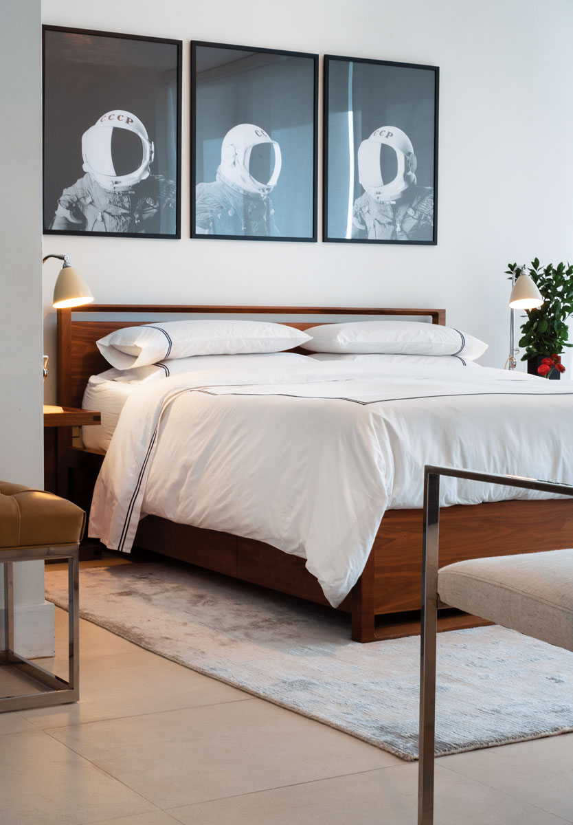 """A pair of vintage metal table lamps from New York's Chelsea Flea Market top the bedside tables in the master suite. A chrome-framed """"Verona"""" armchair and the bench seated in a cognac-hued leather blend beautifully with the walnut frame of the bed."""