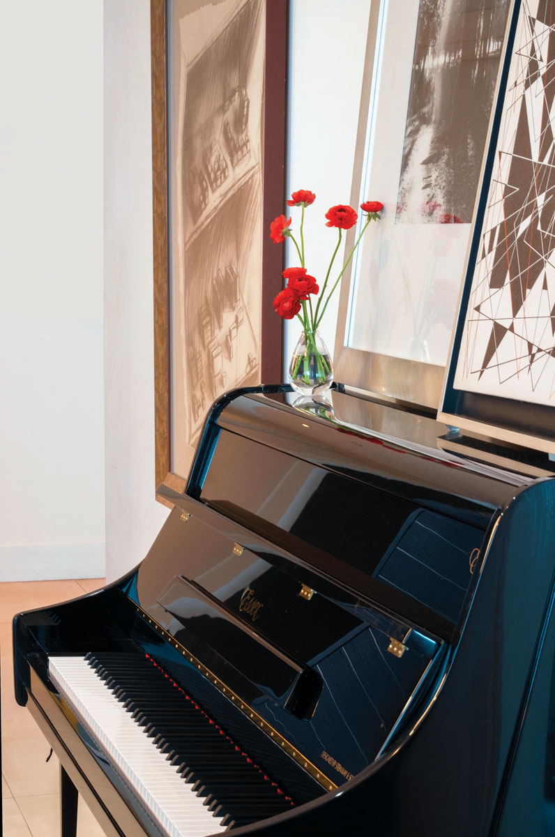 An Essex Upright piano designed by Steinway & Sons is a glamorous centerpiece popular during the designer's cocktail parties.