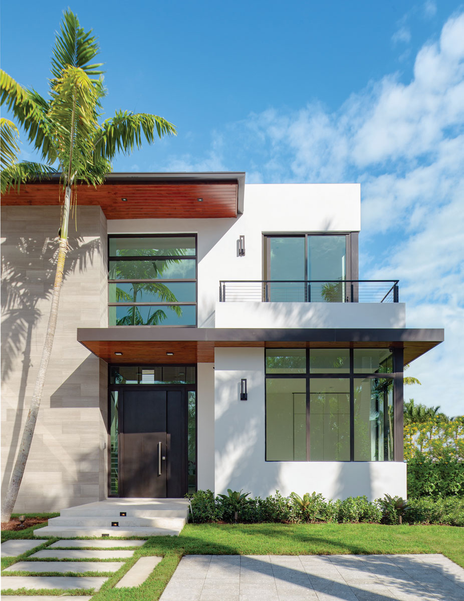 Clad in a contrast of stone, stucco and wood, the front exterior is accented with a solid wood door from Door Galore, sleek balcony railings from Ambiance Interiors, and Modern Forms wall sconces from Brand Lighting.