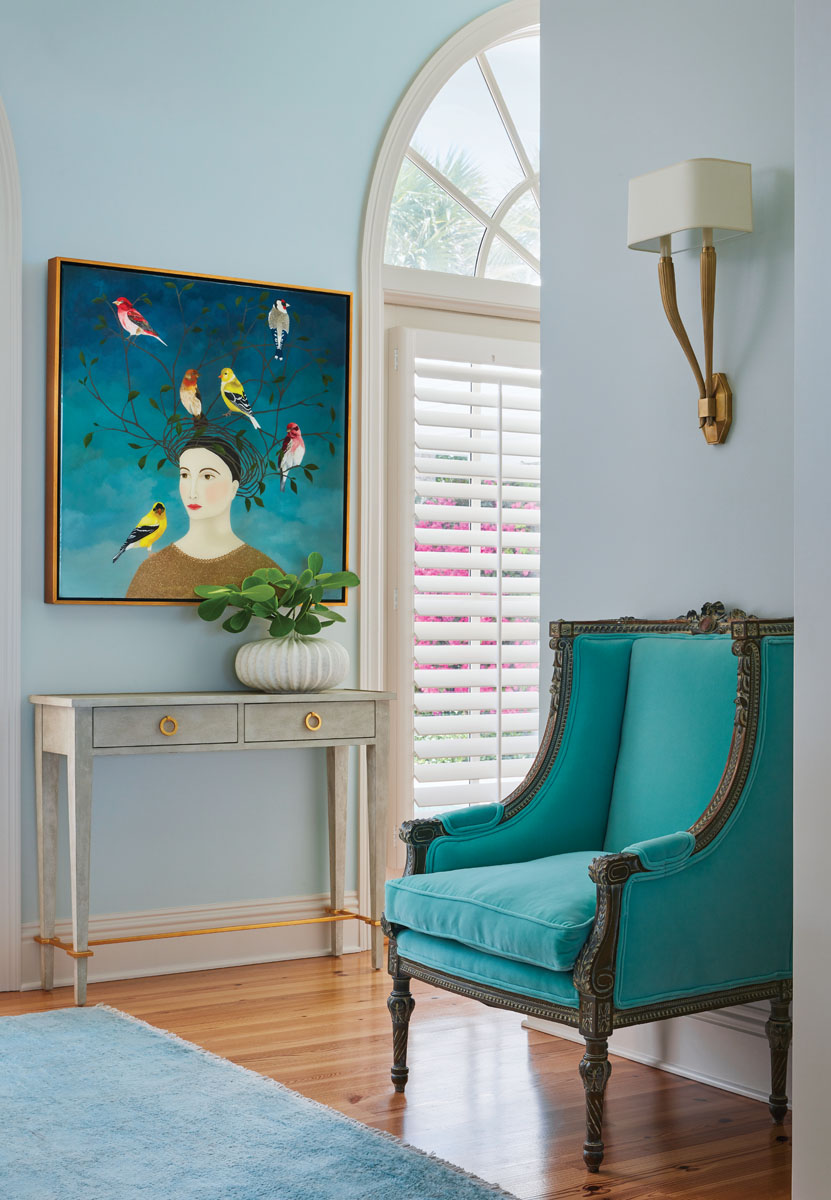 Upon entry, a vintage wingback chair in aqua velvet and Circa Lighting's Art Deco wall sconce join a console from Modern History and an original painting, Storm Watch, by artist Leslie Barron.