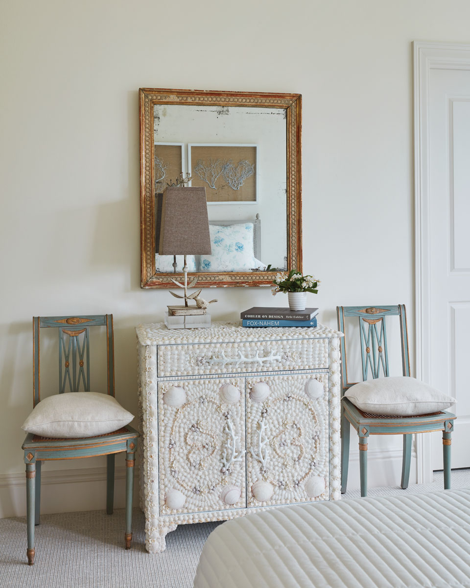 Adding more texture to the guest room, a seashell-encrusted chest from Mecox Gardens is flanked by a pair of antique, pillow-cushioned chairs.